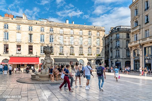 Bordeaux, France - July 22, 2018: Parliament Square or Place du Parlement in French. Crowd of people in historic square featuring an ornate fountain, cafes and restaurants