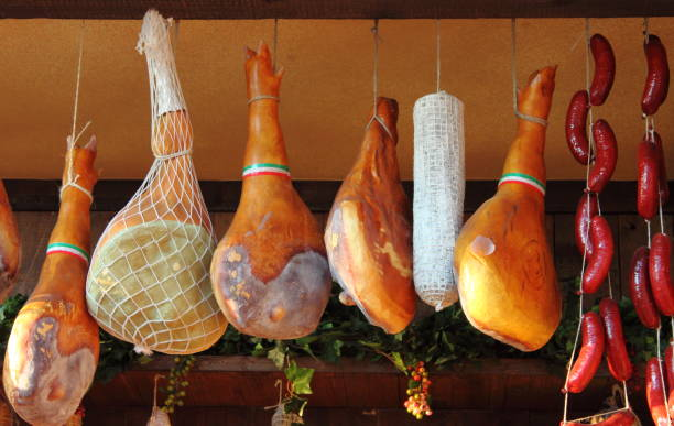 Parma Ham hanging in a delicatessen shop in Italy stock photo