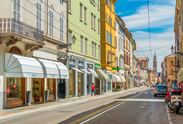 Parma, Italy: A street of Parma  with historical buildings, shops, pharmacy, parked car and scooter stock photo