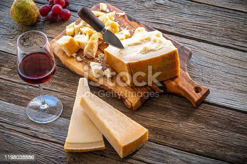 Parmesan Reggiano cheese on cutting board knife with wine and fruits on table
