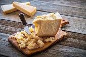 Parmesan Reggiano cheese on cutting board and knife at wooden table