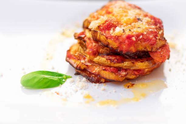 parmigiana di melanzane. traditional italian dish: baked eggplants with parmesan cheese, decorated with fresh basil. - melanzane foto e immagini stock