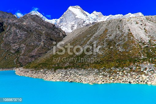 Turquoise Paron lake in Cordillera Blanca, snowcapped mountain range in Peruvian Andes - Ancash region, Peru  Lake Parón is the largest lake in the Cordillera Blanca, on the Peruvian Andes, 32 km E from the city Caraz, at 4185 m asl. It is nested and surrounded by several snow peaks such as Aguja I 5,840 m, Aguja II 5m888 m, Aguja III 5,775 m, Caraz I 6,025 m, Qaras II 6,020 m, Qaras III 5,720 m, Artesonraju 6,025 m, Parón 5,600 m, Pirámide 5,885 m, Chacraraju W 6,112 m, Chacraraju E 6,001 m, Pisco 5,772 m, Huandoy E 6000, Huandoy N 6395 m and Huandoy W 6,356 m. It is one of the most popular areas for climbing in Peru, incThe lake itself is within the borders of the Huascarán National Park. The water level is controlled by a tunnel and underwater gate, to keep water level at 4,155 m asl aiming a double objective: to prevent the overflow and the resulting risk for the downstream population and to manage the river discharge.luding the so famous The Sphinx 5325m, a granite monolith, offering at least 13 big wall routes.