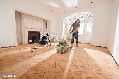 two workers repair and restore a parquet period floor