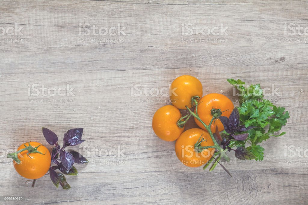 Parsley and basil bunch of bouquets, branch yellow tomatoes on light...
