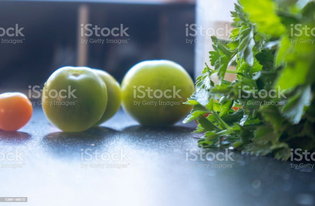 Parsley and green tomatoes stock photo