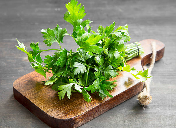 parsley culinary herb on a cutting wooden board - parsley stock photos and pictures