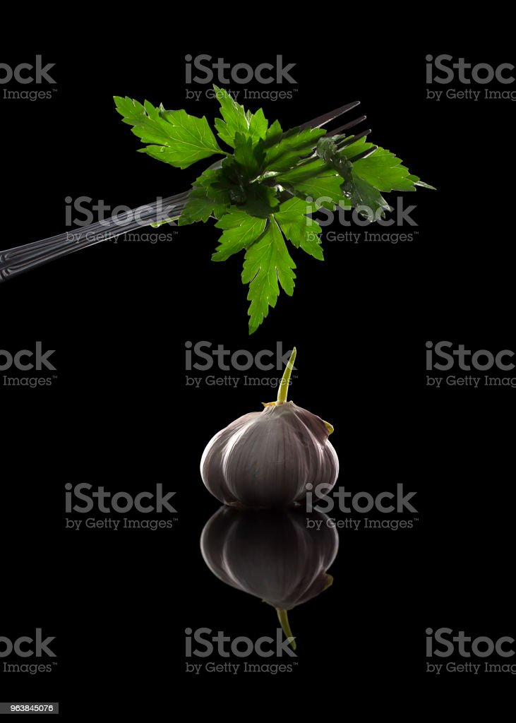 Parsley on a fork and garlic - fresh seasonings for eating, close-up on a black background - Royalty-free Dieting Stock Photo