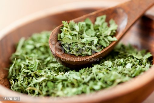 Dried parsley flakes along in a wooden bowl with a wooden spice spoon.