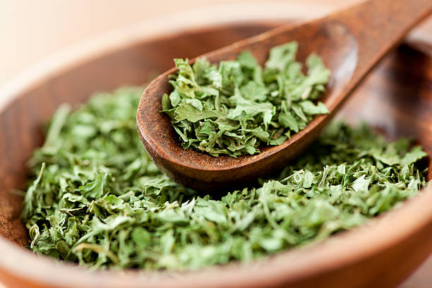 Parsley Dried parsley flakes along in a wooden bowl with a wooden spice spoon. dried plant stock pictures, royalty-free photos & images