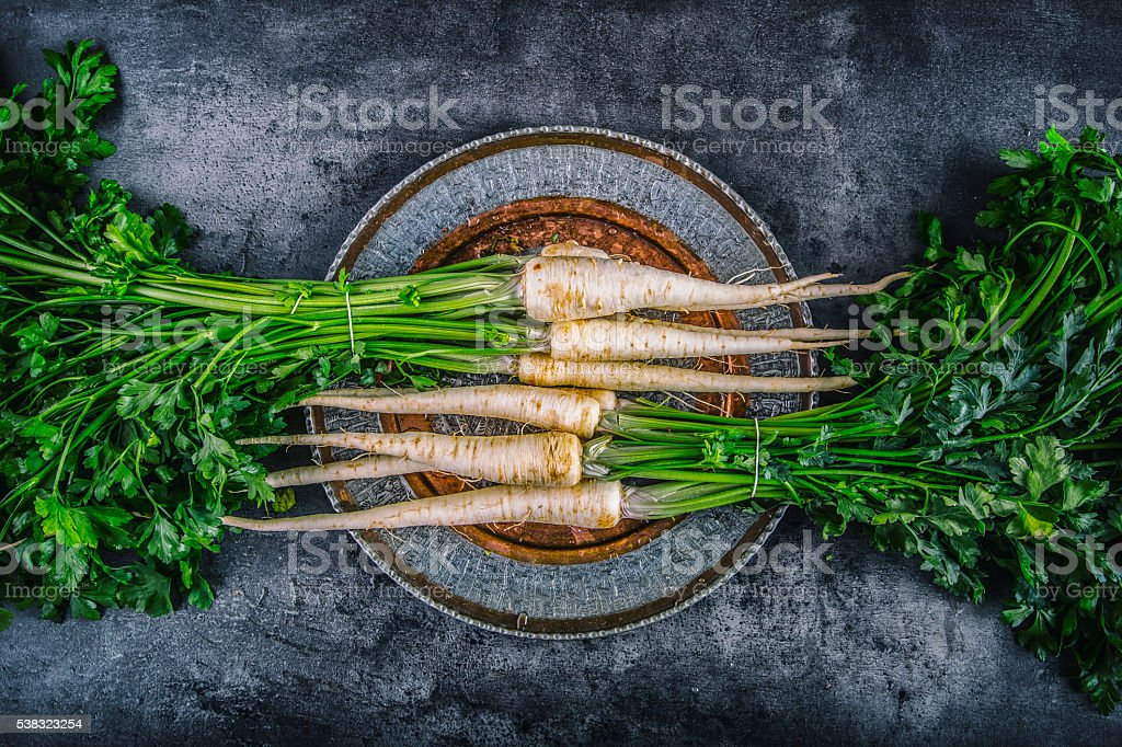 Parsnip. Fresh parsnip. Parsnip with parsley on concrete board. stock photo