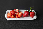 Part chopped and part whole stemmed strawberries set on a small oval plate, healthy breakfast choice, favorite vegan snack packed with vitamins and nutrients, or delicious ingredient in baked goods.
