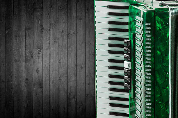 Part green accordion on wooden grey background. Write text stock photo