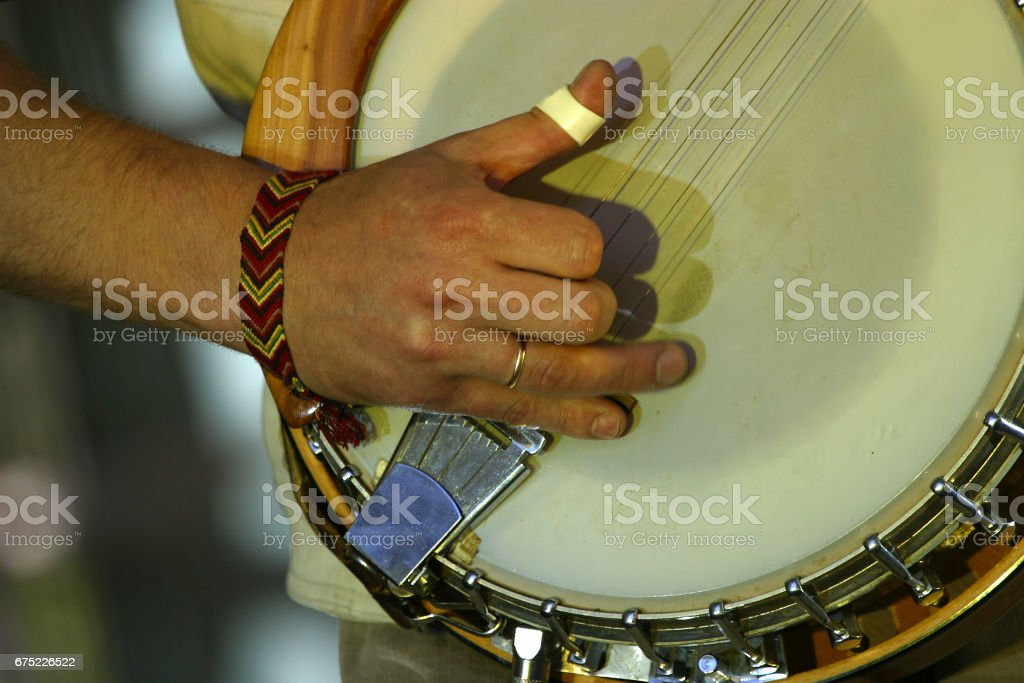 Part of a banjo and hand man close-up royalty-free stock photo