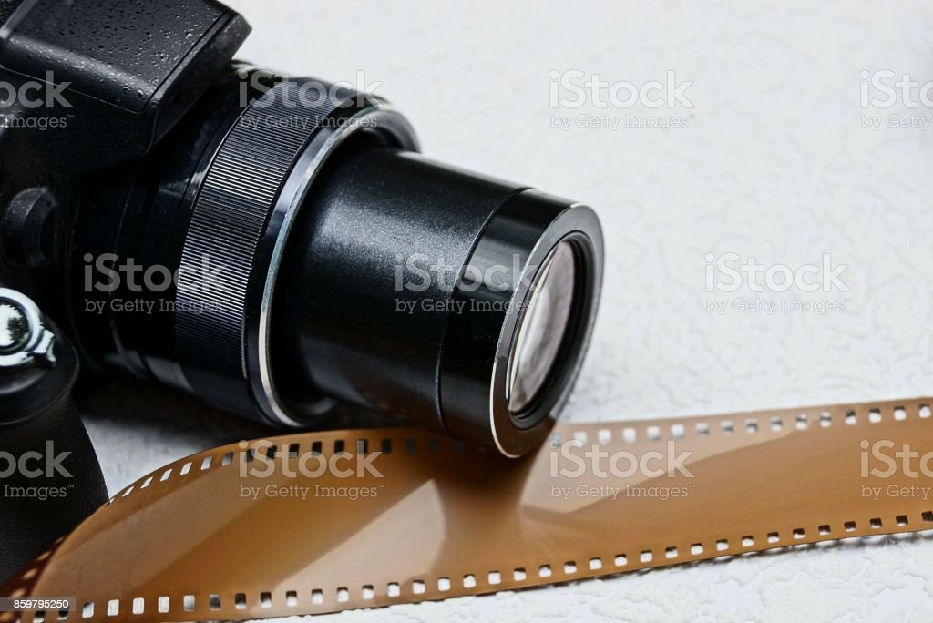 part of a black camera and a brown film on a gray background stock photo