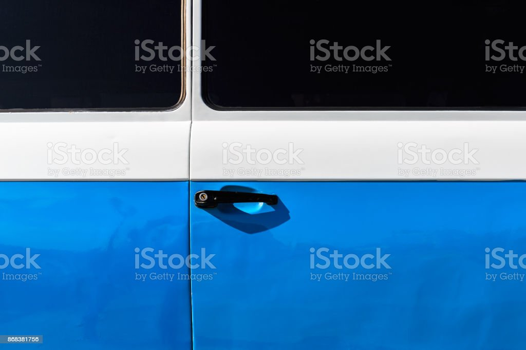 Part of a blue door, lock and black tinted glasses of a vintage car stock photo