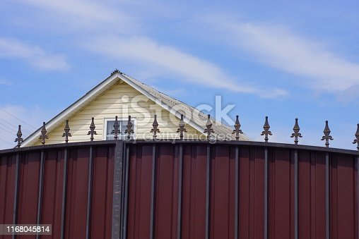 part of a brown metal fence with sharp black rods against the sky