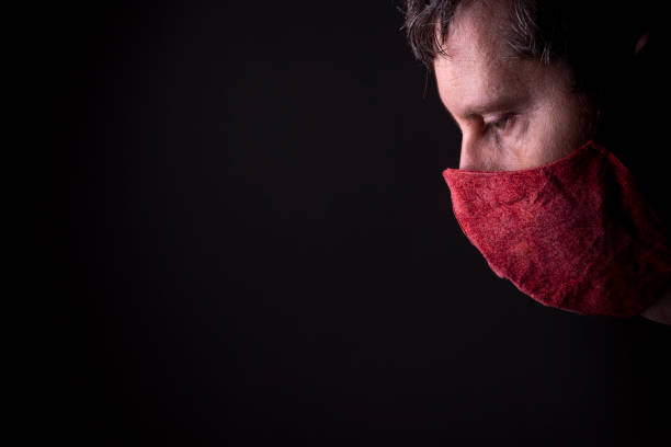 part of a face en profile of a caucasian male looking down with a homemade wrinkled red cloth face mask. - new normal foto e immagini stock