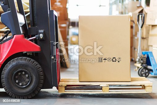 istock Part of a forklift in the form of a wheel and a pitchfork with a large cortone box 903449638