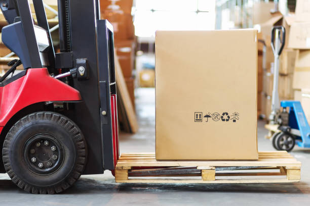 Part of a forklift in the form of a wheel and a pitchfork with a large cortone box stock photo