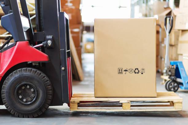en del av en gaffeltruck i form av ett hjul och en högaffel med en stor cortone låda - dagligvaruhandel, hylla, bakgrund, blurred bildbanksfoton och bilder