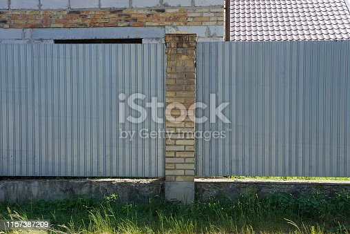 istock part of a gray fence of bricks and metal outside 1157387209