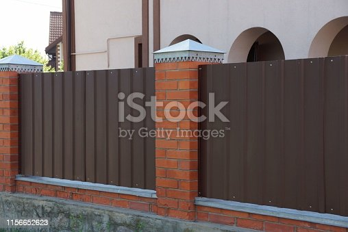 istock part of a private brown metal and brick fence 1156652623