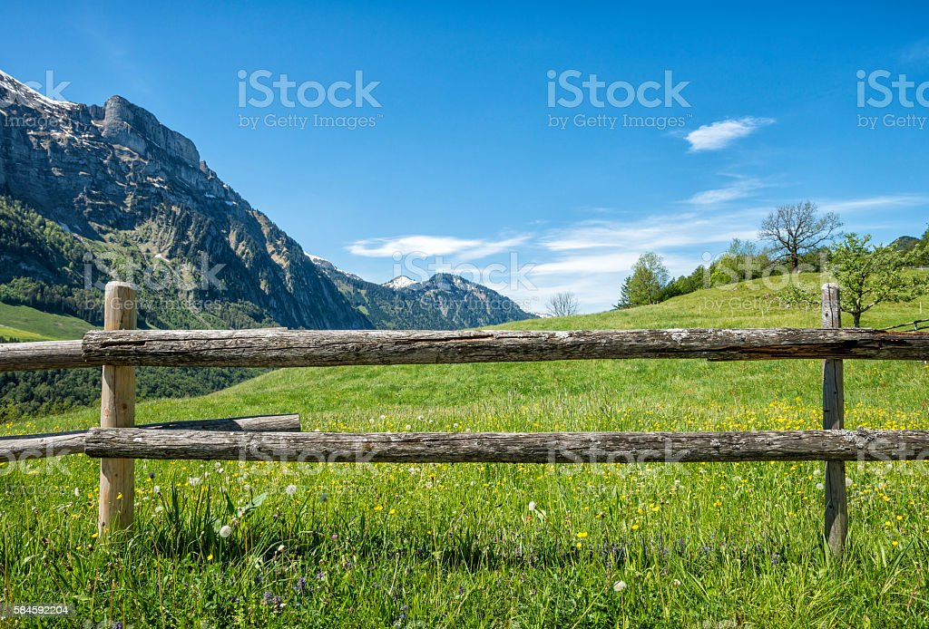 part of a wooden fence on grassy hill stock photo