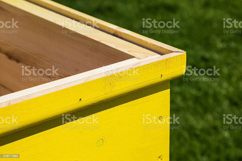 Part of an yellow wooden freshly painted beehive stock photo