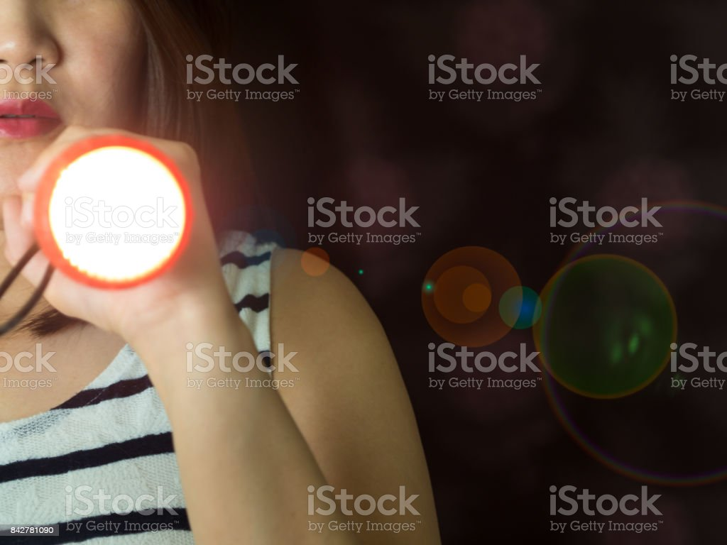Part of Asian woman holding flashlight on left hand peeking the door in the dark stock photo
