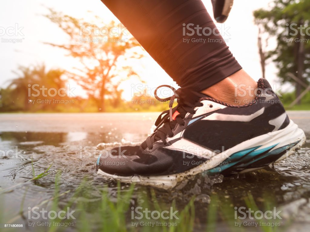 Part of athlete legs and shoes running down on the road, wet floor after the rain at sunset stock photo