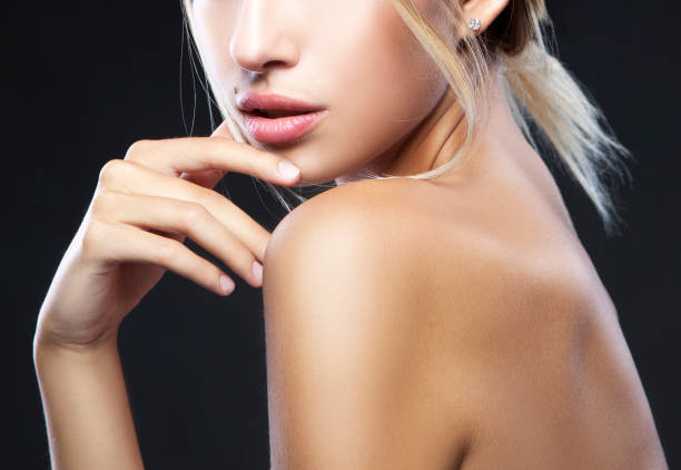 Part of beauty girl face and body Lips, hand and shoulder of beauty model girl. Clean skin, natural make-up. Black background. Skincare facial treatment concept nude women pics stock pictures, royalty-free photos & images