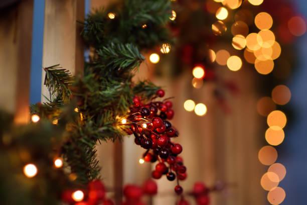 teil der weihnachtsdekoration haus interieur. kranz mit tannen und roten beeren. erleuchtende girlande. - skihütte stock-fotos und bilder
