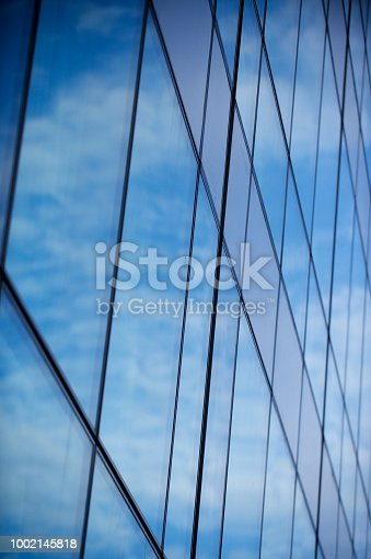 490774222istockphoto Part of contemporary glass skyscraper reflecting the blue sky 1002145818