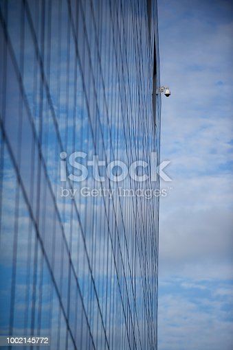 490774222istockphoto Part of contemporary glass skyscraper with security camera reflecting the blue sky 1002145772