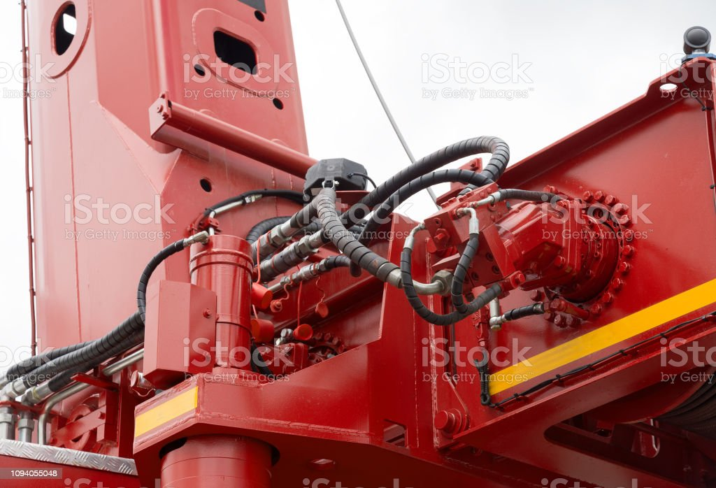 Part of crane machine with red hydraulic pipe