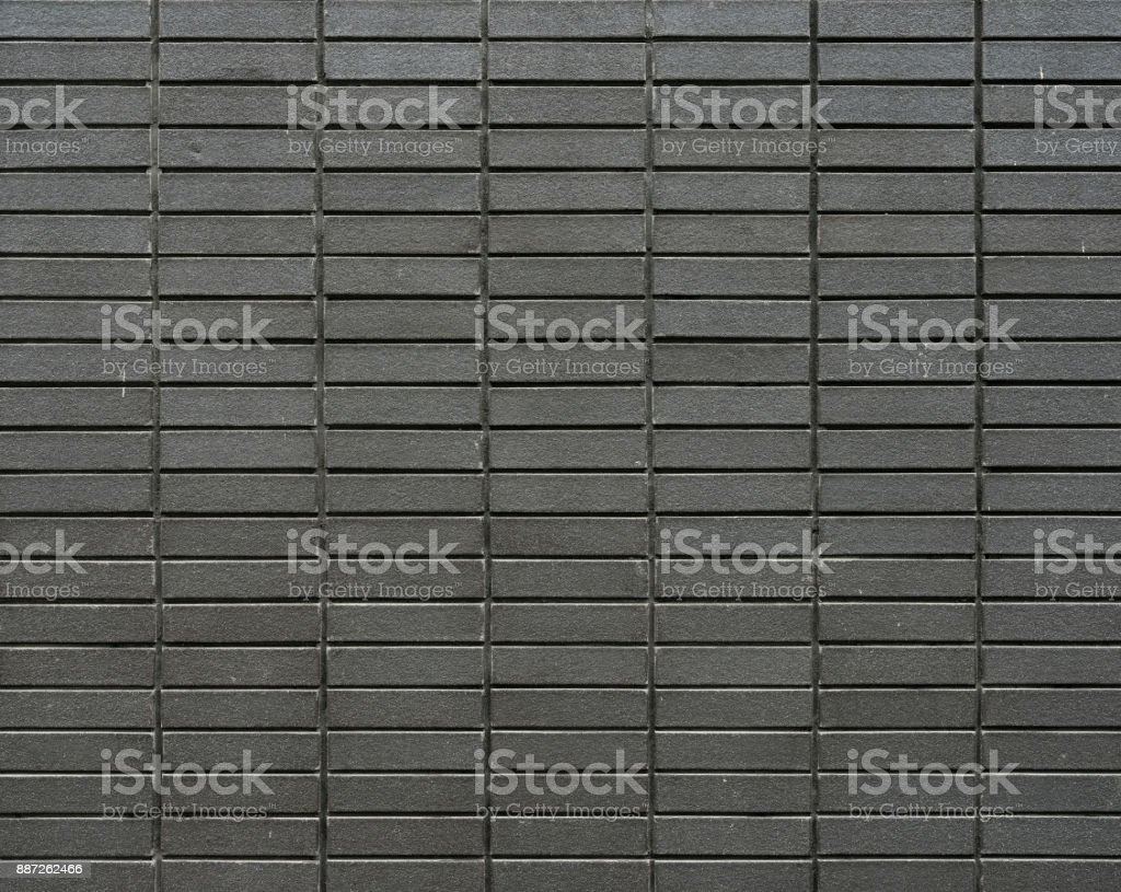 part of grey brown brick wall with strait lines stock photo