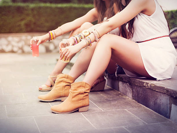part of hippie women sitting on curb - hippie fashion stock photos and pictures