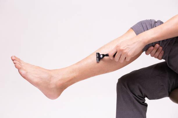 Teil der menschlichen Beine zu rasieren und entfernen Beinhaare mit Rasieren Rasiermesser in weiß isoliert Hintergrund. – Foto