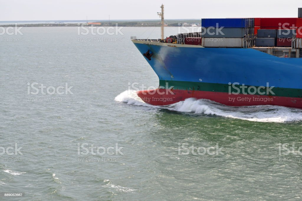 Part of large merchant ship container vessel in coastal waters of ocean. A merchant ship is moving around sea in daytime stock photo