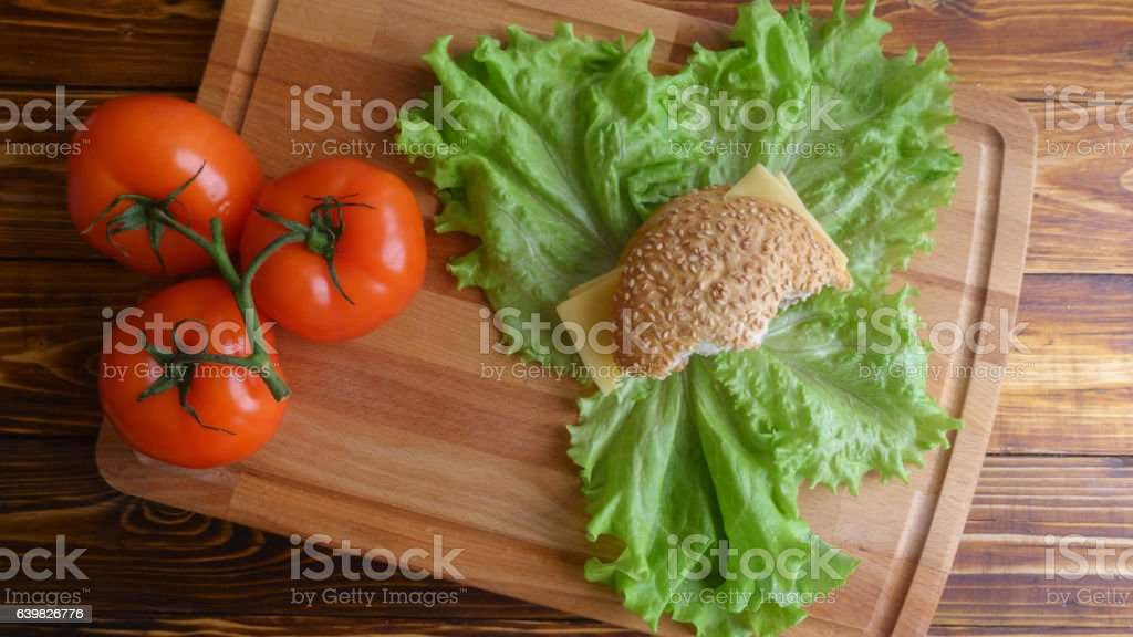 Part of natural fastfood hamburger top view on salad leaves stock photo