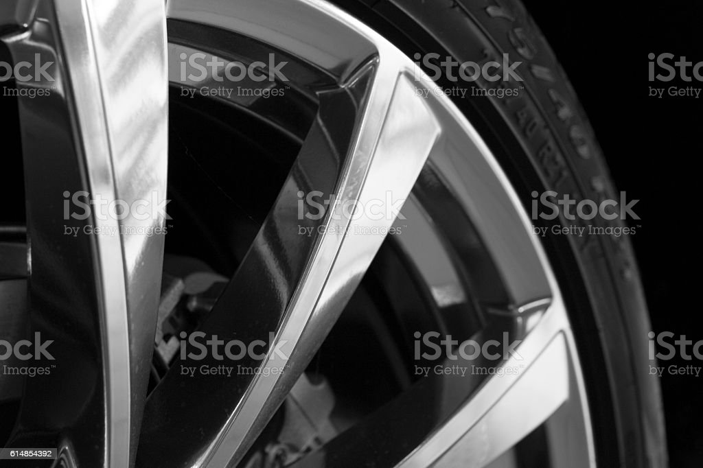 Part of new tire on alu rim on black stock photo