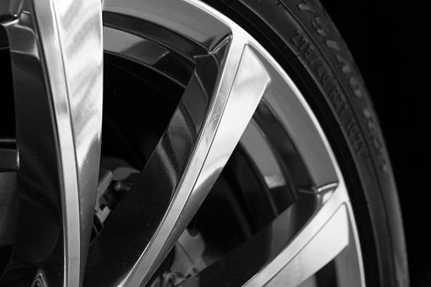 Part of new tire on alu rim on black stock photo