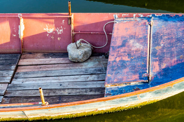 Part of old weathered fishing boat Part of old weathered fishing boat with a concrete deadweight anchor at the Kladovo Marina, Danube River, Serbia deadweight stock pictures, royalty-free photos & images