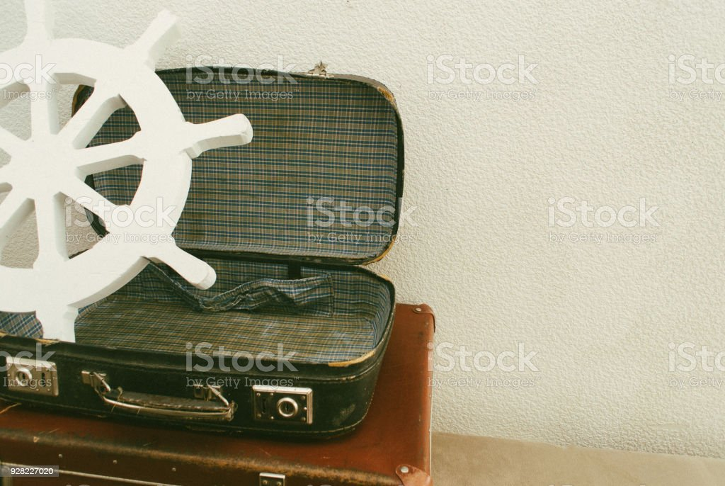 Part of open leather travel valises or old suitcase with vintage white steering wheel . Close up stock photo