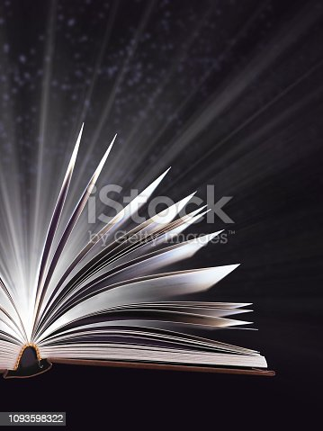 528363897istockphoto Part of open magic book, bewitched book glows in the darkness, magic light. Education. Dreamy image of a fairytale 1093598322