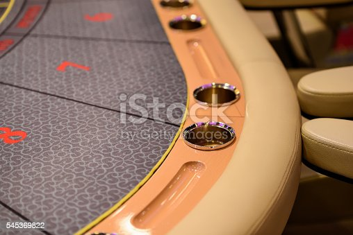A part of poker table with cupholders and ashtray