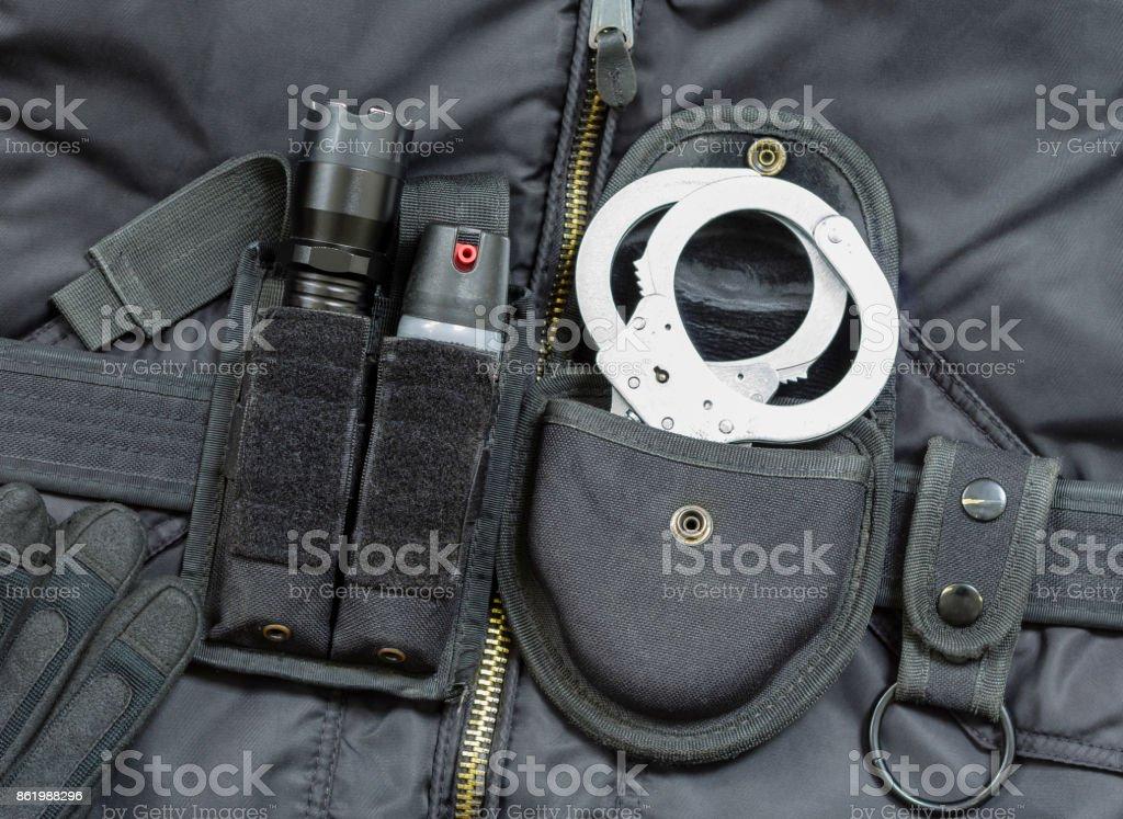 Part of Police officer equipment. Tear gas spray, flashlight with stun gun, handcuffs. stock photo