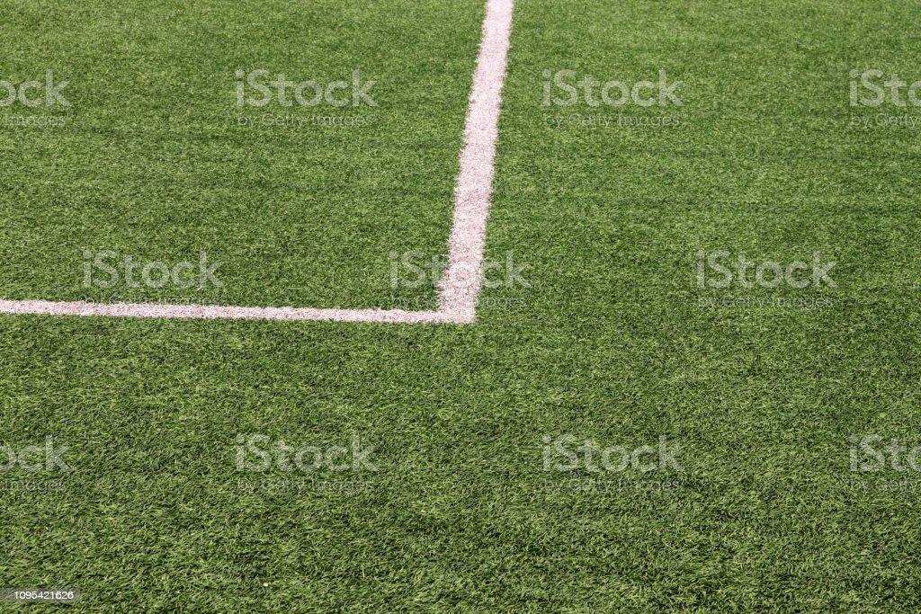 Parte do estádio de futebol do esporte e campo de futebol de relva artificial. Detalhe, close-up de grama verde com linhas brancas, a linha do gol, linha de canto. Campo de futebol de foco selecionado fundo, textura, papel de parede. - foto de acervo
