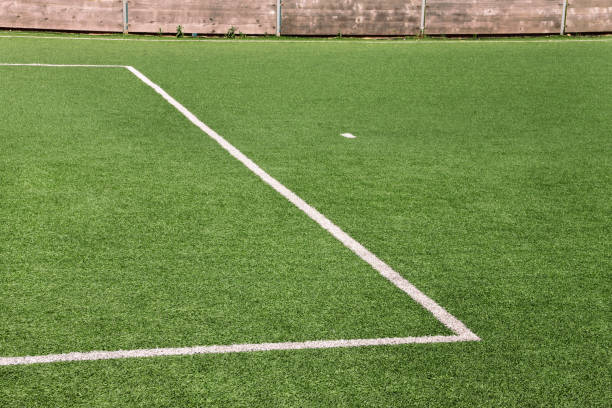 Part of sport soccer stadium and artificial turf football field. Detail, close up of green grass with white lines, goal line, corner line. Focus football field selected background, texture, wallpaper. stock photo